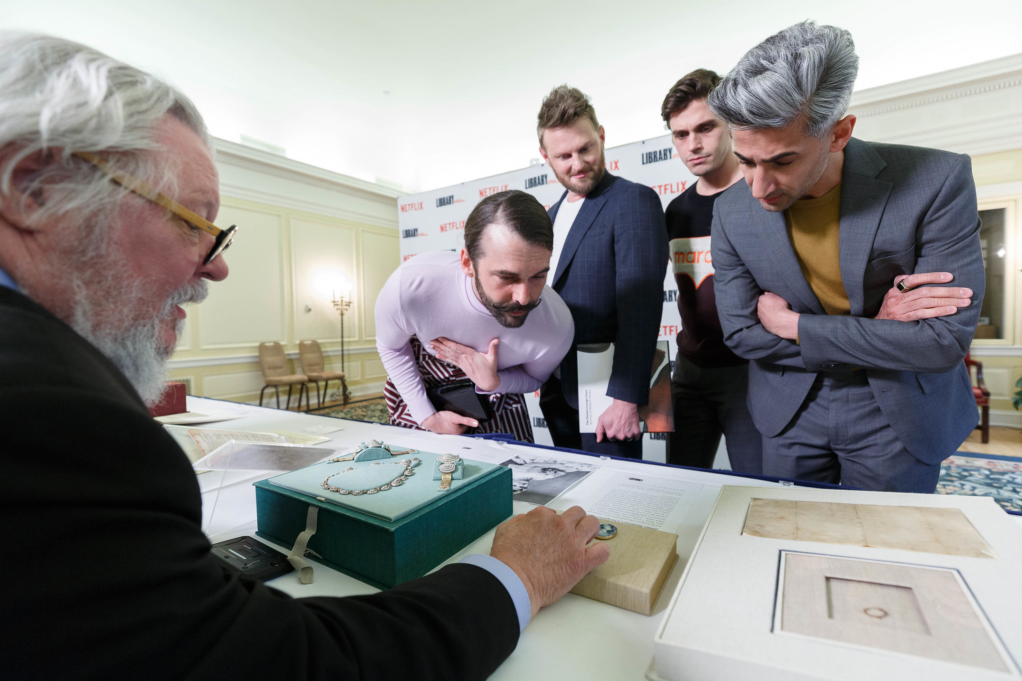 The cast of Queer Eye Season 5 look over a collections display in the Whittall Pavilion, April 3, 2019.